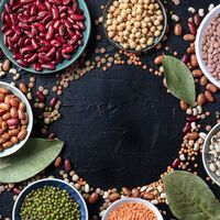 Legumes, top shot on a dark background with copy space. Lentils, soybeans, chickpeas, red kidney beans, a vatiety of pulses with bay leaves, forming a square frame