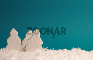 Three white wooden trees with snow on a green paper background, space for text on top
