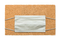 Blank Welcome Mat With Medical Face Mask Isolated on White Amidst The Coronavirus Pandemic