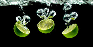 Bunch of lime fruits halves splashing with bubbles into water isolated against black background