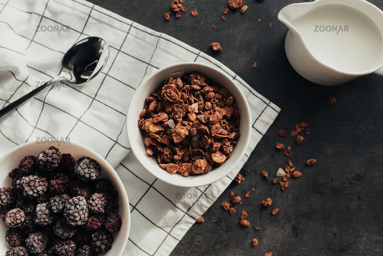 Frozen blackberries, granola, cream, towel on table. Blurred background
