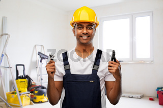indian builder in helmet with wrench and pliers