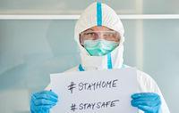 Arzt in Schutzkleidung mit #stayhome und #staysafe Schild
