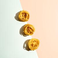 Pasta art with tagliatelle on pastel duotone background