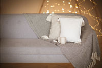 Comfortable sofa with cushions and white mug of hot drink in cozy living room