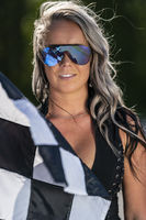 Beautiful Blonde Model Waves A Checkered Flag With Colored Smoke In The Background During A Street Race On A Sunny Day