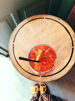 Anonymous female and goblet of alcohol cocktail with cherries and black straw