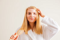 Hair care and treatment concept. Beautiful blonde woman brushing her hair