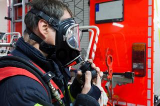 Feuerwehrmann setzt sich eine Atemschutzmaske auf