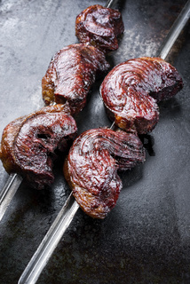 Barbecue dry aged wagyu Brazilian picanha from the sirloin cap of rump beef offered as closeup on a skewer on a rustic old board