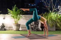 Asian woman do yoga in city at night