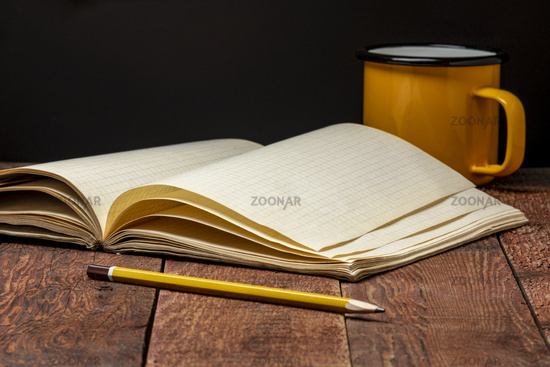 old blank notebook and tea cup on a rustic table