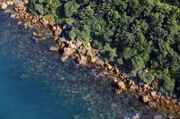 Aerial view of turquoise sea water and rocky coastline. Summer vacation concept.