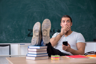 Young male teacher student sitting in the classroom