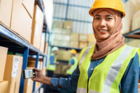 Islam muslim female warehouse worker use mobile phone scan qr code for online inventory