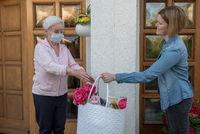 Seniorin mit Mundschutz bekommt Einkäufe von junger Nachbarin