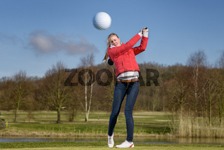 Golferin schlägt auf Golfplatz ab