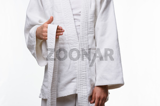 Stages of correct tying of the belt by a teenager on a sports kimono, step one