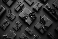 Dark Christmas theme. Square boxed gifts wrapped in black paper and ribbon arranged on black