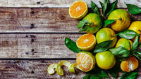 Green mandarins on wooden background, top view