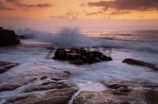 Coastal sunrise waves crashing onto rocks