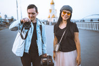 Happy tourists with suitcase on embankment of river. Young man takes photo. Woman wearing casual clothes smiling looking at camera. Traveling concept