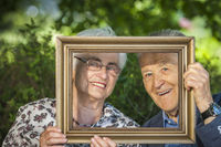 Retired couple looks through frame