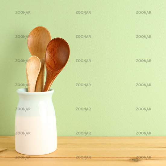 Wooden spoons in holder on wooden table with green background