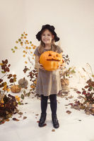 Little funny girl in witch costume on scene