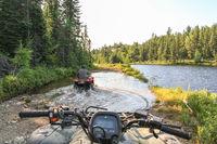 People driving ATV quads through water. Lake in Ontario, Canada.