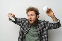 No coffee in inverted cup good looking man with curly hair and beard holding cup, wearing plaid long sleeve shirt isolated on white background. Crisis and lockdown concept