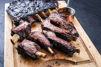 Traditional Barbecue burnt beef ribs St Louis style sliced and offered as close-up on a rustic wooden board