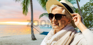 happy senior woman in sunglasses and hat on beach