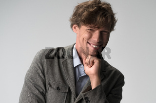 Handsome man rejoices and laughs with his chin on his fist. Studio portrait