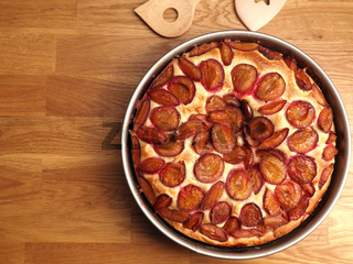 Delicious plum cake made from organic ingredients in a baking pan on a rustic kitchen table