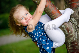 Little girl in a blue dress hanging on a tree branch