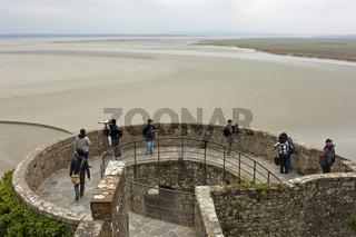 Besucher blicken von einem Turm der Abtei Mont St. Michel auf das Wattenmeer bei Ebbe