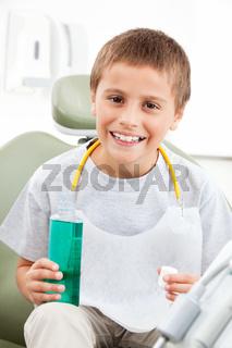 Kind mit Mundwasser beim Zahnarzt