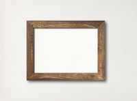 Old rustic wooden picture frame hanging on a white wall