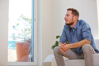 Mann sitzt zu Hause im Wohnzimmer