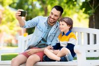 father and son taking selfie with phone at park
