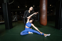 Two beautiful young girls doing fitness in a gym. Stretching the muscles of the legs and arms.