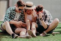 Three Young Friends Are Sitting On The Grass Outdoors And Looking At Mobile Phone.