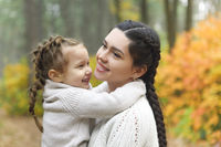 Mother and daughter play in autumn park. Parent and child walk in the forest on a fall day