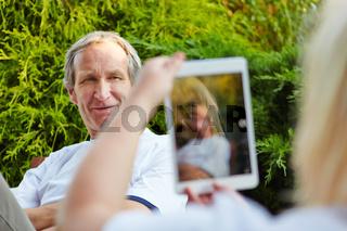 Paar im Urlaub mit Fotos mit Tablet Computer