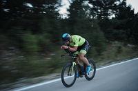 triathlon athlete riding bike at night