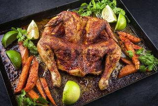 Traditional barbecue spatchcocked chicken al mattone chili with sweet potato chips and limes offered as close-up on an old rustic metal tray