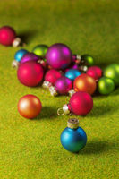 Small christmas balls on green grass