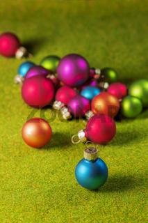 Small christmas balls on green grass