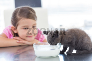 Girl looking at kitten drinking milk from bowl